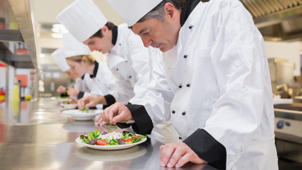 Chef's preparing their salads in the kitchen